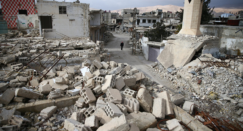 A man walks past damaged buildings in the rebel held besieged city of Douma, in the eastern Damascus suburb of Ghouta, Syria January 8, 2017