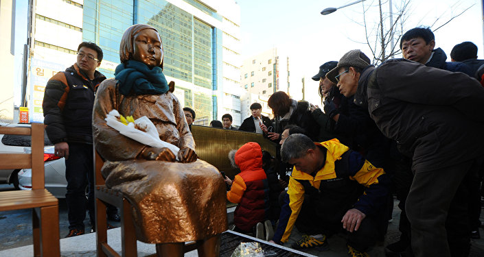 A flower is laid on a statue of a girl that represents the sexual victims by the Japanese military during a rally in front of Japanese Consulate in Busan, South Korea, December 30, 2016. Picture taken December 30, 2016
