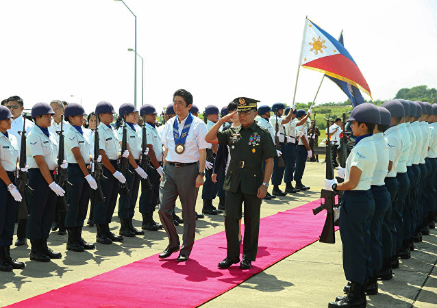Japan's Prime Minister Shinzo Abe is accompanied by Major General Leonardo Guerrero of the Philippine Army as they walk past the guard of honour before his departure from the Francisco Bangoy International Airport in Davao City, southern Philippines January 13, 2017