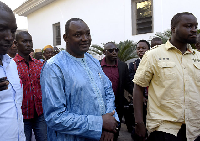 Gambian president-elect Adama Barrow (C), flanked by his supporters arrives at a hotel in Banjul, for a meeting with four African heads of state on December 13, 2016
