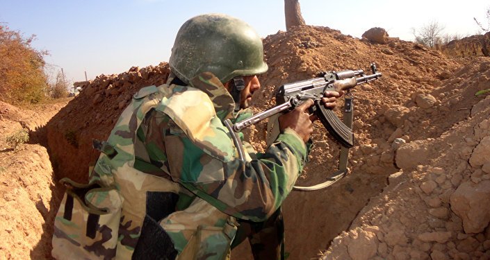 A Syrian army soldier takes aim in the government sector of the town of Houwayqa, which is besieged by Islamic State (IS) group jihadists, in the northeastern Syrian city of Deir Ezzor (File)