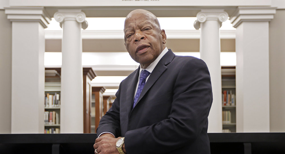 Rep. John Lewis, D-Ga., poses for a photograph under a quote of his that is displayed in the Civil Rights Room in the Nashville Public Library Friday, Nov. 18, 2016, in Nashville, Tenn.