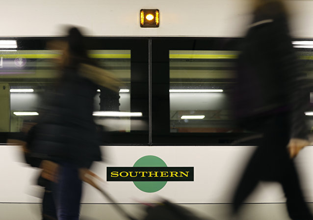 Travelers pass a train as Southern railway workers are on strike at Victoria Station in London