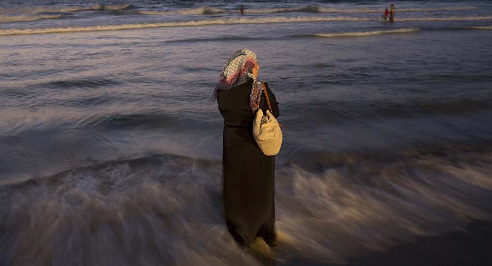 A Palestinian woman stands in the water on the beach during the Muslim Eid al-Adha holiday, in Tel Aviv, Israel, Wednesday, Sept. 14, 2016.
