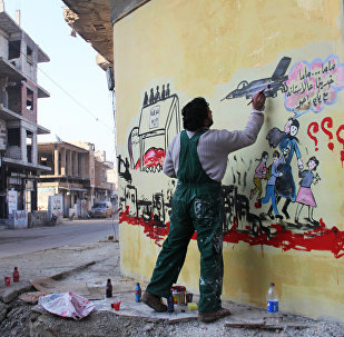 Syrian artist Aziz al-Asmar works on a mural depicting the war in his country ahead of the start of the Astana peace talks, on January 19, 2017, in the Syrian rebel-held town of Binnish, on the outskirts of Idlib