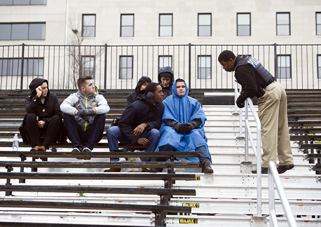A Secret Service officer speaks with people sitting on the Inaugural parade stands in Washington, DC.