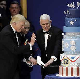President Donald J. Trump, left, and Vice President Mike Pence, right, are helped by Coast Guard Petty Officer 2nd Class Matthew Babot, center, as they cut a cake at The Salute To Our Armed Services Inaugural Ball Friday, Jan. 20, 2017, in Washington.