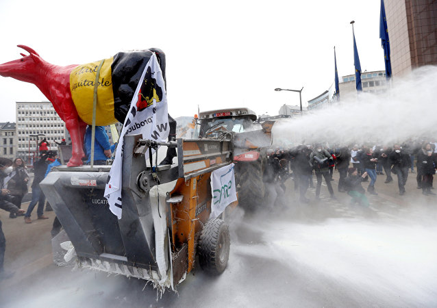 Milk producers spray powdered milk to protest against dairy market overcapacity outside a meeting of European Union agriculture ministers in Brussels, Belgium