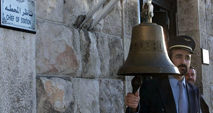 A Syrian railway station employee rings the bell (file)