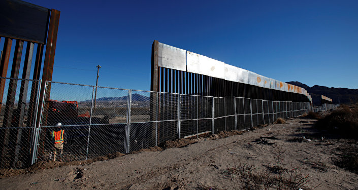 A worker stands next to a newly built section of the U.S.-Mexico border fence at Sunland Park, U.S. opposite the Mexican border city of Ciudad Juarez, Mexico