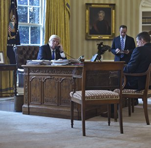 US President Donald Trump speaks on the phone with Russia's President Vladimir Putin from the Oval Office of the White House on January 28, 2017, in Washington, DC