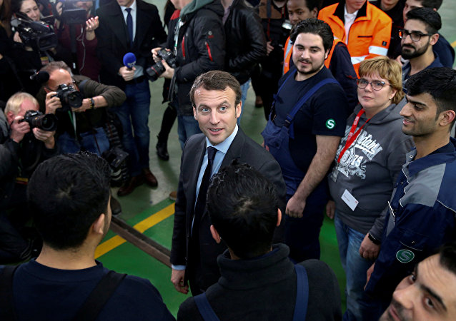 Emmanuel Macron (C), head of the political movement En Marche !, or Forward !, and candidate for the 2017 French presidential election, smiles during a visit to a qualification class for refugees of German railway operator Deutsche Bahn in Berlin, Germany January 10, 2017