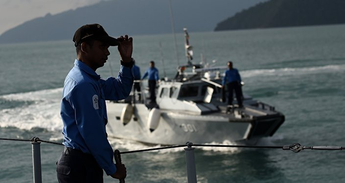 A Royal Malaysian Navy sailor (L) gestures as he stands aboard a naval ship during a search and rescue mission for boat-people, near the Thai-Malaysia border north of Langkawi island on May 28, 2015