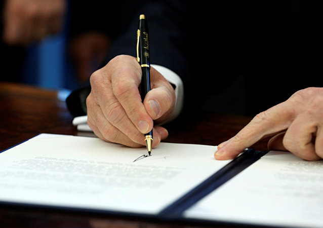 US President Donald Trump signs a memorandum.