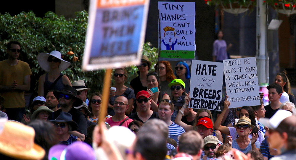 Protesters hold placards as they stand together in Sydney, Australia, February 4, 2017 during one of several rallies across Australia condemning U.S. President Donald Trump's order temporarily barring refugees and nationals from seven countries and demanding an end to Australia's offshore detention of asylum seekers