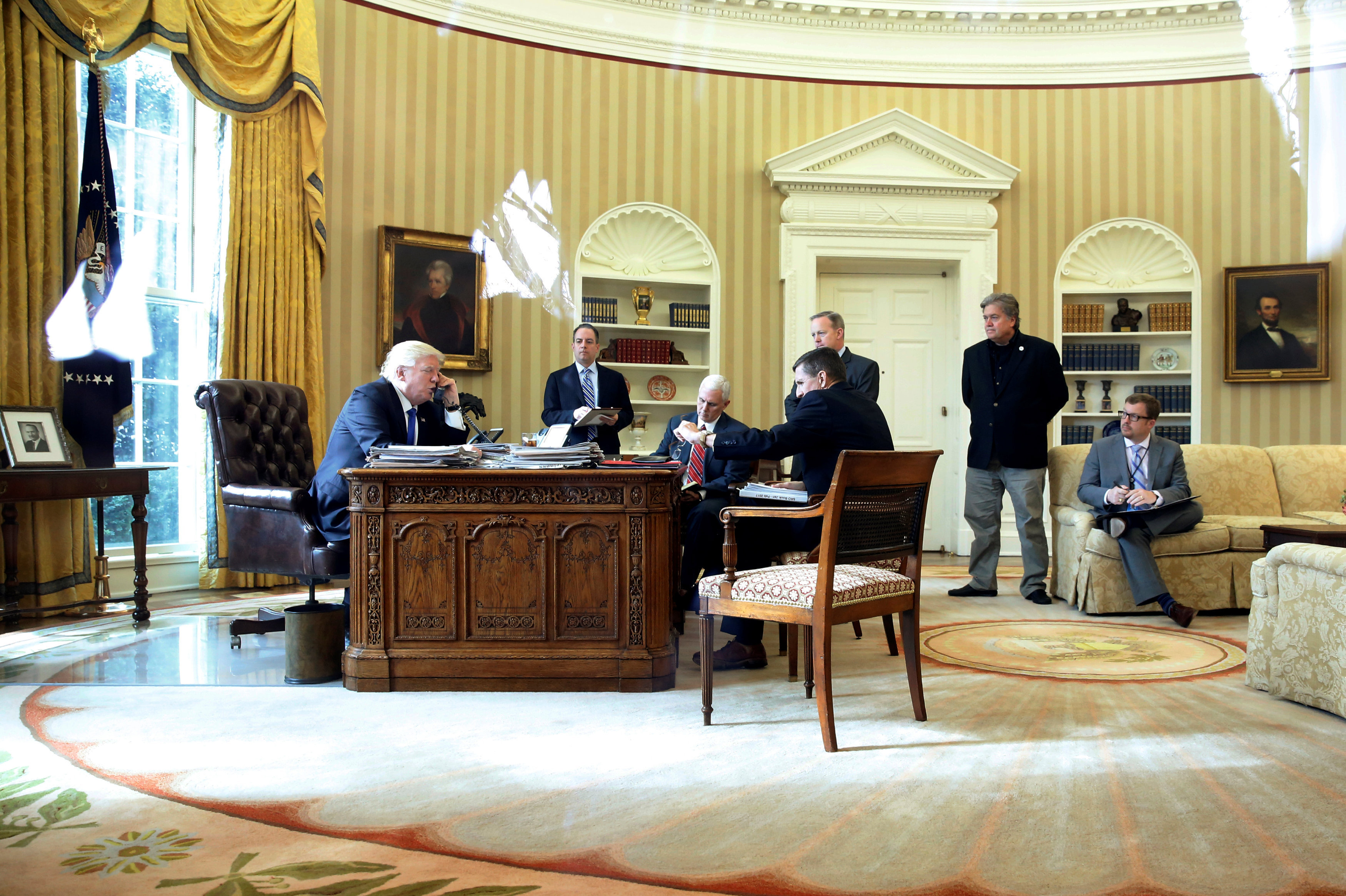 U.S. President Donald Trump (from L), joined by Chief of Staff Reince Priebus, Vice President Mike Pence, National Security Advisor Michael Flynn, Communications Director Sean Spicer and senior advisor Steve Bannon, speaks by phone with Russia's President Vladimir Putin in the Oval Office at the White House in Washington, U.S. January 28, 2017