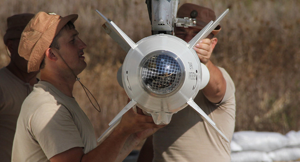 Russian servicemen attach a Kh-25 high-precision missile to a Su-24 aircraft at the Khmeimim airbase in Syria