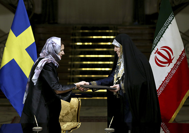 Sweden's Minister for EU Affairs and Trade Ann Linde, left, and Iran's Vice President for Women and Family Affairs Shahindokht Molaverdi shake hands after signing documents at the Saadabad Palace in Tehran, Iran, Saturday, Feb. 11, 2017