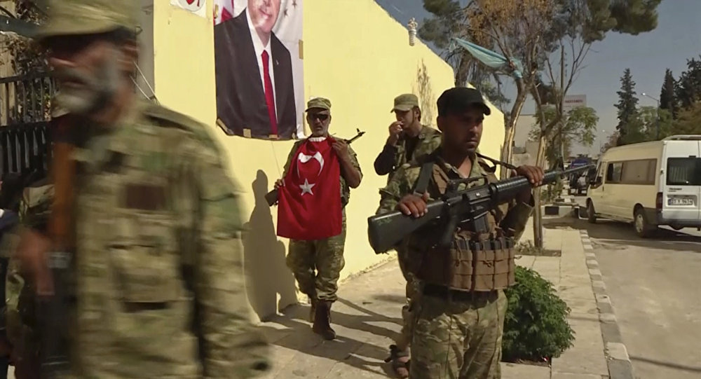 Turkish-backed Syrian opposition forces, one carrying a Turkish flag, patrol in Dabiq, Syria (File)