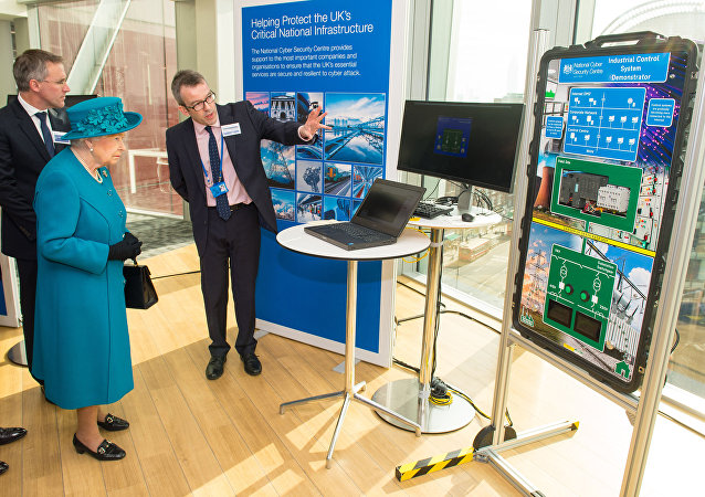 Britain's Queen Elizabeth II (2L) listens as Director of Engagement and Advice Alex Dewdney (R) explains how an electricity supply could be subjected to cyber attack, as she attends the opening of the National Cyber Security Centre in London on February 14, 2017.