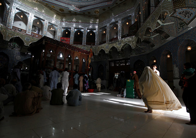 A woman clad in burqa walks in the hallway of the tomb of Sufi saint Syed Usman Marwandi, also known as Lal Shahbaz Qalandar, in Sehwan Sharif, in Pakistan's southern Sindh province. (File)