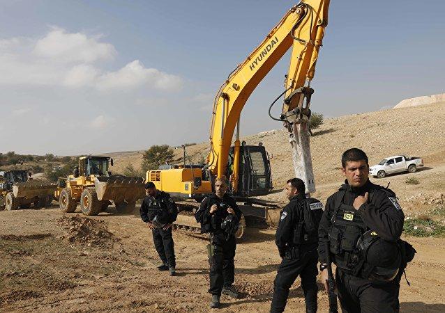 Israeli policemen stand guard next to bulldozers (File)