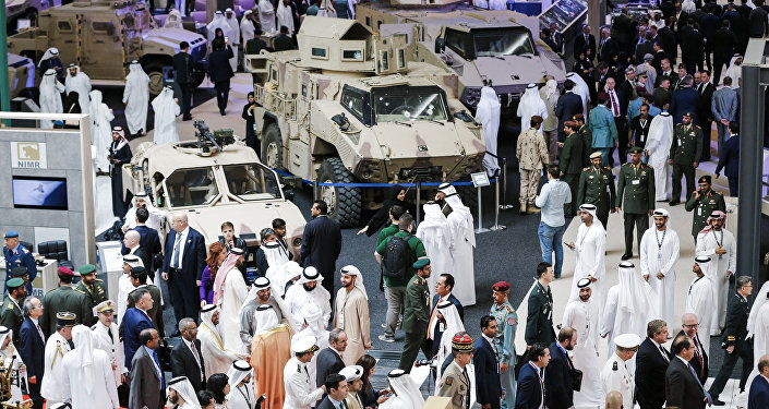 A picture taken on February 19, 2017 shows a general view of visitors walking in a showroom displaying armoured military vehicles during the opening of the International Defence Exhibition and Conference (IDEX) in the Emirati capital Abu Dhabi