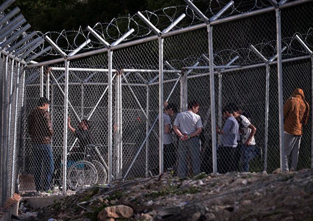 Migrants stand behind a fence at the VIAL detention center on the island of Chios where migrants and refugees arrived after the March 20 EU-Turkey deal are kept, on April 4, 2016