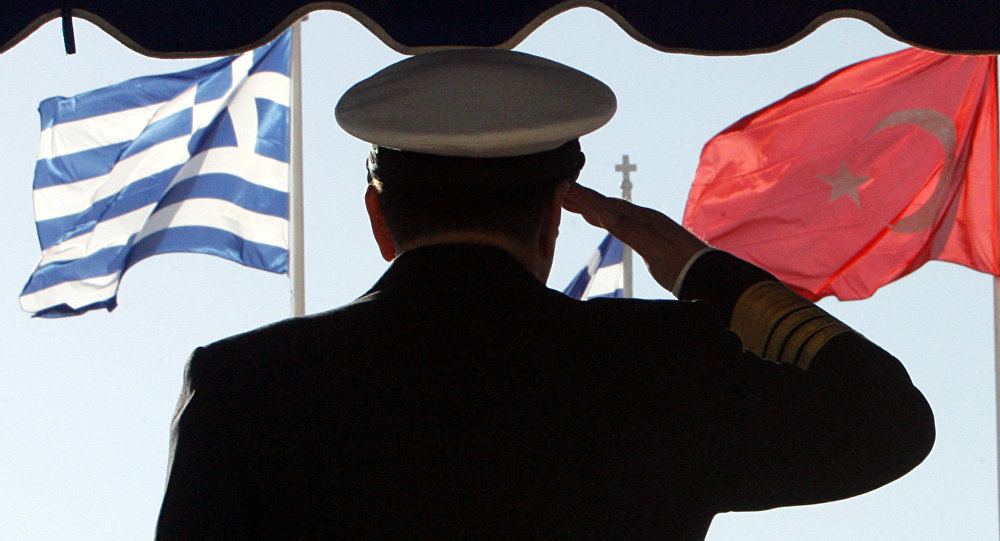 Greece's military Adm. Panagiotis Chinofotis salutes during the Turkish national anthem as the Greek, left, and Turkish flags wave at the Greek Defense Ministry in Athens on Thursday, Nov. 2, 2006