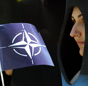 A activist holds a NATO flag during a demonstration in Istanbul, Turkey, Saturday, June 26, 2004.