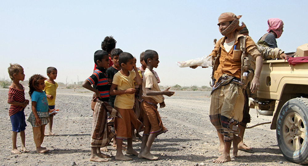 Pro-government fighters give food to Yemeni children on the road leading to the southwestern port city of Mokha on January 26, 2017
