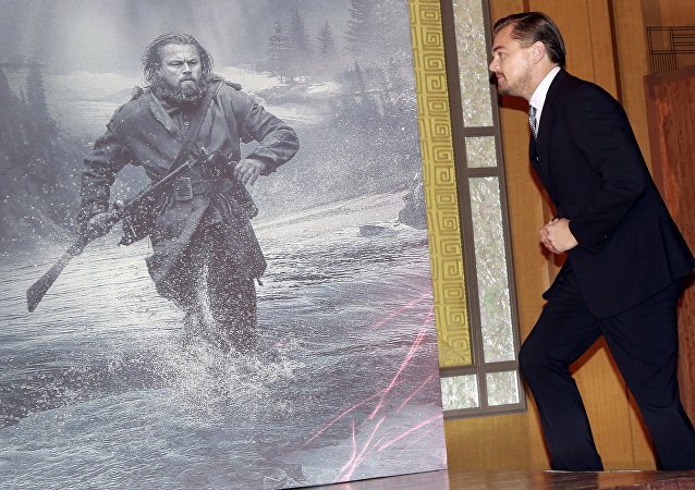 """Actor Leonardo DiCaprio walks in the stage during a news conference of the movie """"The Revenant"""" in Tokyo, Wednesday, March 23, 2016"""