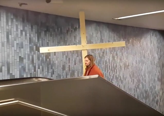 'Jesus' gets his cross stuck in underground station roof as he travels up the escalator in hilarious