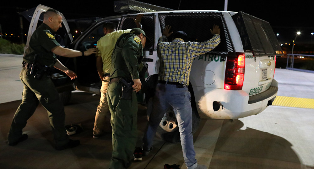 U.S. border patrol agents detain two men from India after they entered the United States by climbing over the border wall from Mexico in Calexico, California, U.S. February 8, 2017