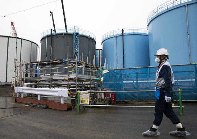 A Tokyo Electric Power Co.'s (TEPCO) employee walks past storage tanks for contaminated water at the company's Fukushima Dai-ichi nuclear power plant in Okuma, Fukushima, Japan, on February 23, 2017