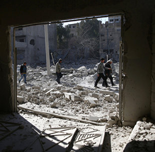 People walk at an area hit by airstrikes in the rebel held besieged Douma neighbourhood of Damascus, Syria. (File)