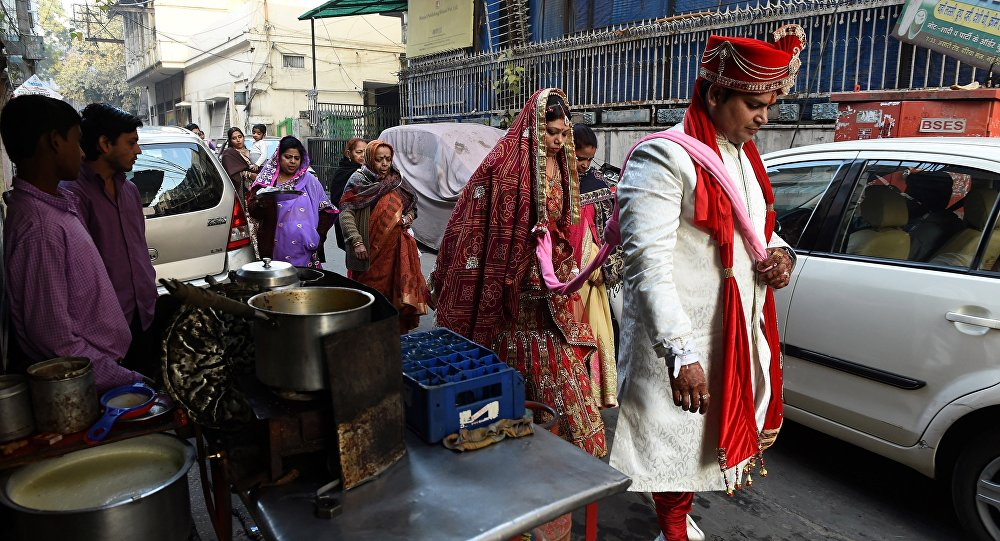 Newly married Indian man Rohit Aggarwal (R) is watched by relatives and street vendors as he leads his wife Shally Aggarwal (2R) to their home after visiting a temple in New Delhi on February 16, 2017