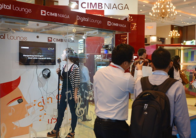 A visitor (L) sings a song at karaoke booth (File)
