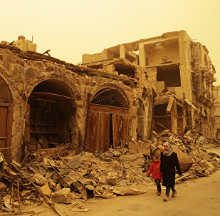 Syrian girls walk past destruction during a sandstorm in the once rebel-held Bab al-Nasr neighbourhood in the old part of Aleppo on March 10, 2017