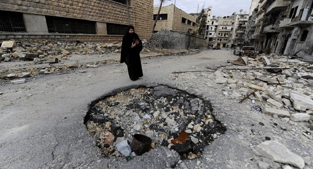 A Syrian woman walks past a destroyed building in Aleppo. File photo