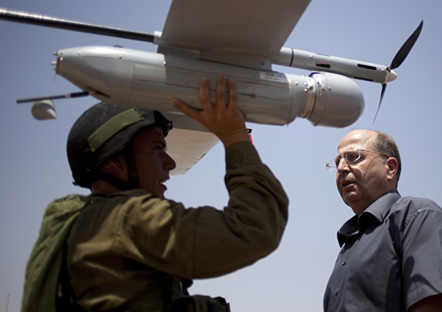 In this July 9, 2013 file photo, an Israeli soldier holds up a Skylark I (Rochev Shamayim) unmanned drone as part of a demonstration for Israel's Defense Minister Moshe Yaalon, center, in an urban warfare army training facility, near Zeelim, southern Israel.