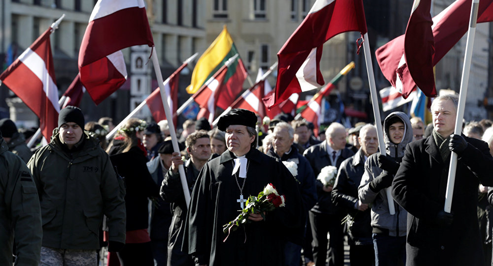 People hold flags, as they participate in the annual procession commemorating the Latvian Waffen-SS (Schutzstaffel) unit, also known as the Legionnaires, in Riga, Latvia March 16, 2017