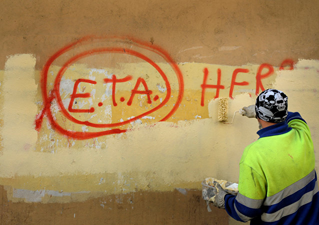 A municipal worker paints over graffiti reading ETA, The People Are With You in the Basque town of Guernica, Spain.