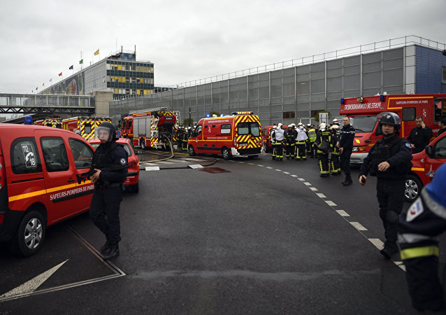 French policemen and firefighters secure the area at Paris' Orly airport on March 18, 2017 following the shooting of a man by French security forces