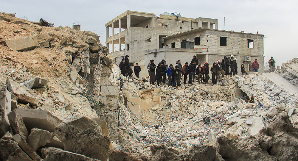People stand by as Syrian civil defence volunteers, known as the White Helmets, dig through the rubble of a mosque following a reported airstrike on a mosque in the village of Al-Jineh in Aleppo province on March 17, 2017