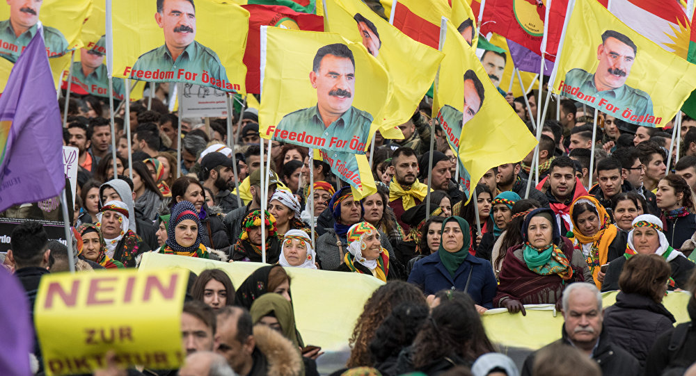 Kurdish protesters demonstrate on their way to the Kurdish spring festival Newroz with placards reading No to dictatorship and the portrait of the leader of the Kurdistan PKK Workers' Party, Abdullah Ocalan in the city center of Frankfurt am Main, western Germany, on March 18, 2017