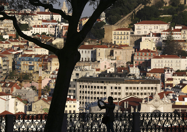 A woman taking pictures from a public garden is silhouetted against the buildings in Lisbon's old town center Wednesday evening, March 15, 2017.