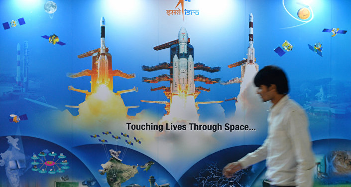 A man walks past a poster of Indian Space Research Organisation (ISRO)