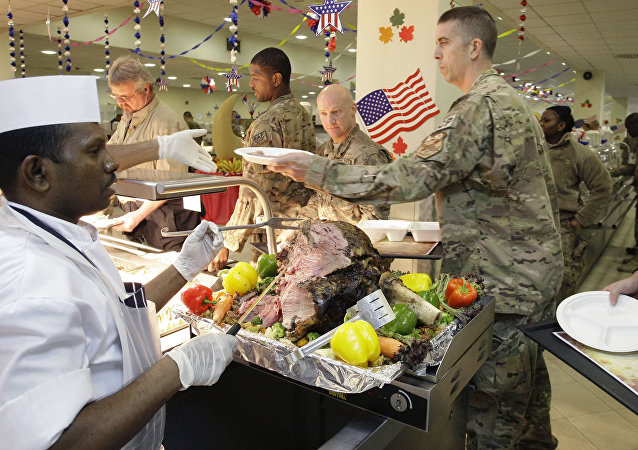 A dining facility worker, left, serves meat to soldiers and civilians for their Thanksgiving meal at the US-led coalition base in Kabul, Afghanistan, Thursday, November 22, 2012.
