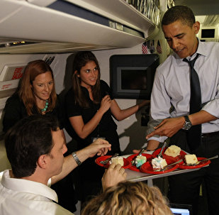 Obama serves birthday cake to ABC correspondent Jake Tapper, left, while serving the press corps on his birthday